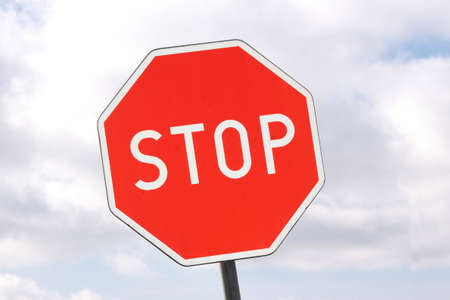 Road sign - stop - on cloudy sky background photo