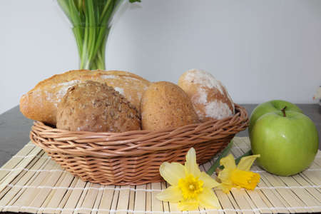 Variety of whole wheat bread in basket and greena apples photo