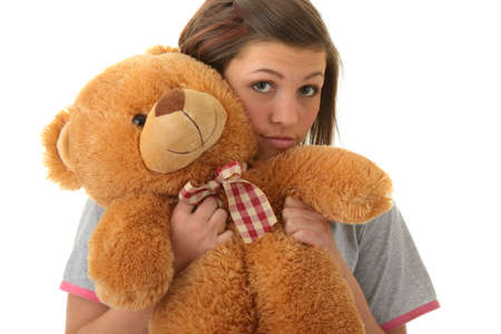 Beautiful teenager holding a teddy bear - isolated on white background photo