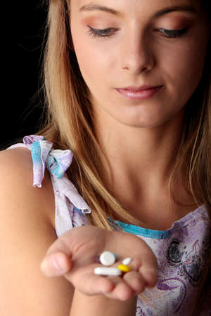 Young woman holding lot of pills isolated on black background - focus on face Stock Photo - 5361390