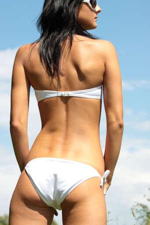 Sexy young woman in white bikini agaist clear blue sky photo