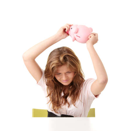Young beautiful woman siting at the desk with piggy bank (money box), isolated on white background photo