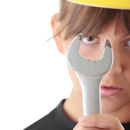 Young woman builder at work with big french key, isolated on white - focus on key photo