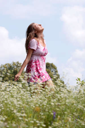Smile teen open hands standing on field ful of flowers   photo