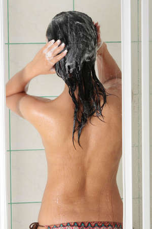 Young woman in shower washing her hairs photo