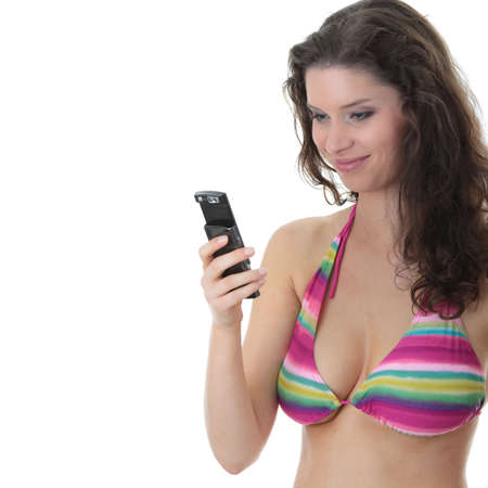 Beautiful Young Woman Wearing A Colorful Bikini Top Using A Mobile Cellphone Isolated Over White photo