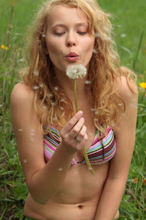 The blonde sits in park on a grass with a dandelion in hands ang blowing   photo