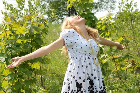 Young beautiful blond woman wearing black and white dress enjoying the sun photo