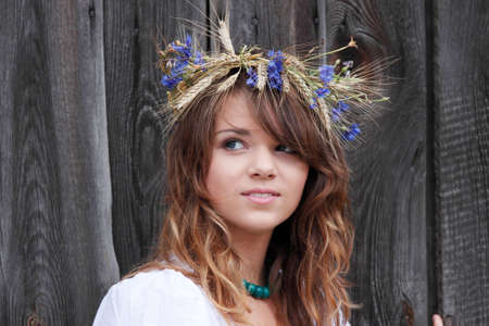 corn flower: Beautiful young girl with grain wreath against old wood wall