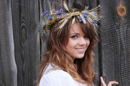 Beautiful young girl with grain wreath against old wood wall photo