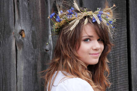 Beautiful young girl with grain wreath against old wood wall Stock Photo - 5394007