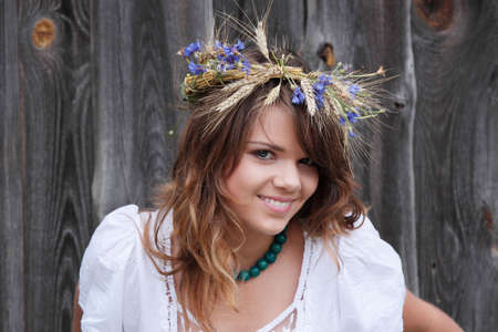 Beautiful young girl with grain wreath against old wood wall Stock Photo - 5394014