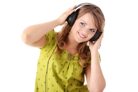 Beautiful teenage girl in a green dress listening to music with big headphones, isolated on white Stock Photo - 5393992