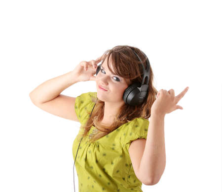 Beautiful teenage girl in a green dress listening to music with big headphones, isolated on white photo