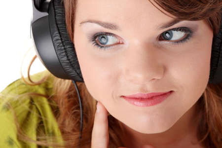 Beautiful teenage girl in a green dress listening to music with big headphones, isolated on white Stock Photo - 5393979