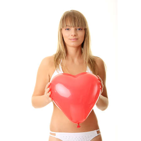 Happy young woman in bikini with heart shaped balloon - valentines concept photo
