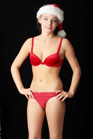 Woman in red bra and panties with santa hat  On black background  photo