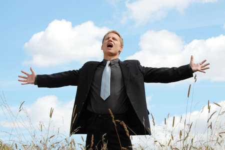 A successful business man with his arm outstretched on a field photo