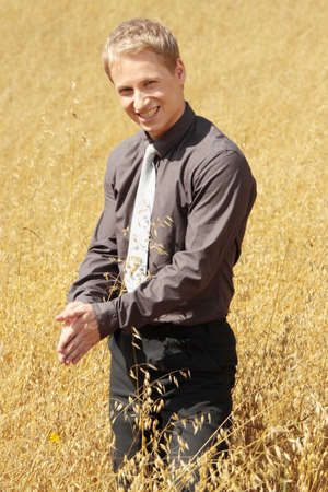 Young modern farmer in suit standing in field of oats   photo
