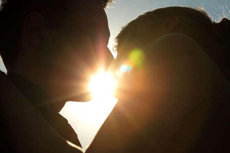 young couple kissing: Silhouette of a young couple kissing with the sun setting behind them Stock Photo