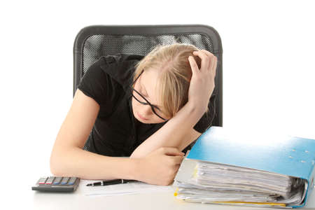 Female executive filling out tax forms while sitting at her desk. Isolated photo