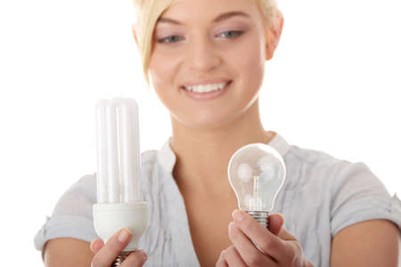 Teen girl environmentalist comparing one compact fluorescent light bulb to incandescent light bulb  photo