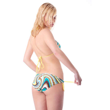 Young beautiful tanned blond warm woman in bikini photo