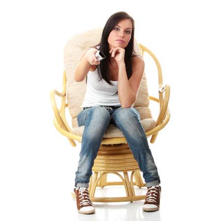 mujeres sentadas: Joven viendo TV con control remoto en la mano mientras sesi�n del sill�n aislado - vista de TV - cambiar el concepto de canal Foto de archivo