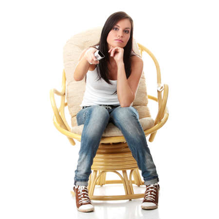 remote: Young woman watching TV with remote control in hand while sitting on armchair isolated - view from TV - Change the channel concept