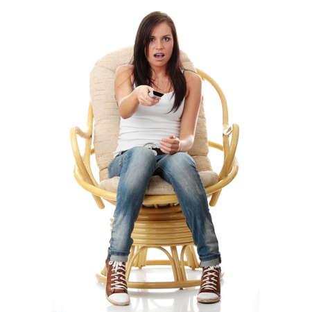 mujeres sentadas: Joven viendo TV con mando a cambiar el concepto de canal en la mano mientras sesi�n del sill�n - sorprendido o asustado, aislado - vista desde la TV-