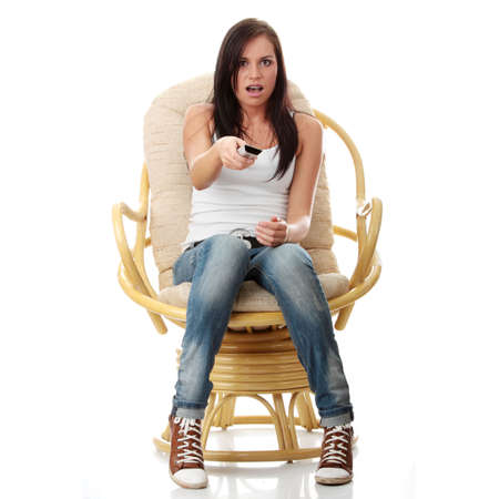 woman watching tv: Young woman watching TV with remote control in hand while sitting on armchair - surprised or scared ,isolated - view from TV - Change the channel concept Stock Photo