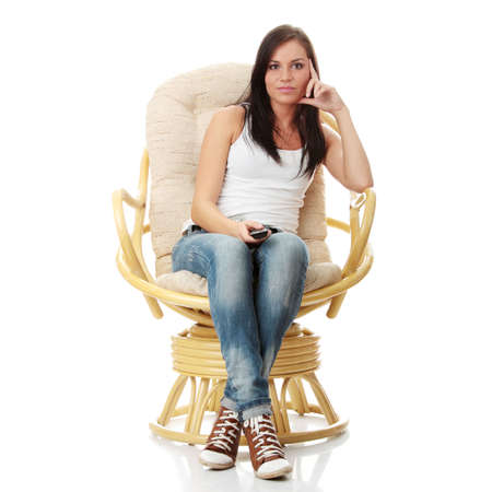 changing channel: Young woman watching TV with remote control in hand while sitting on armchair isolated - view from TV - Change the channel concept
