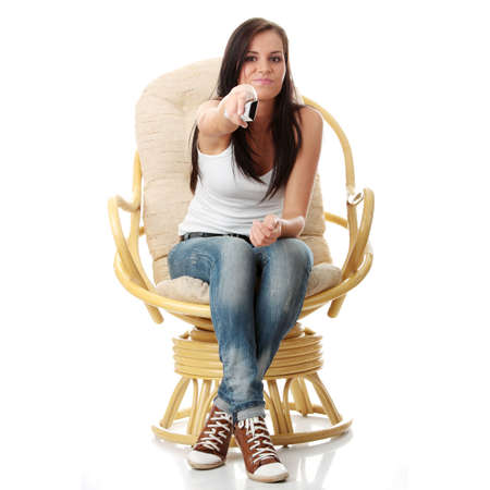 Young woman watching TV with remote control in hand while sitting on armchair isolated - view from TV - Change the channel concept photo