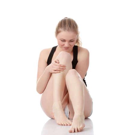 aktywność fizyczna: Piękne młoda kobieta blond doświadczającym Kurcz nóg po aktywności fizycznej, odizolowane na białym tle  Zdjęcie Seryjne