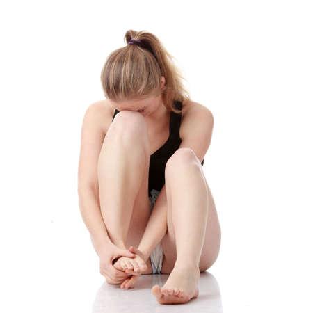 douleur main: Belle jeune femme blonde �prouvant des crampes de jambe apr�s une activit� physique, isol�e sur fond blanc