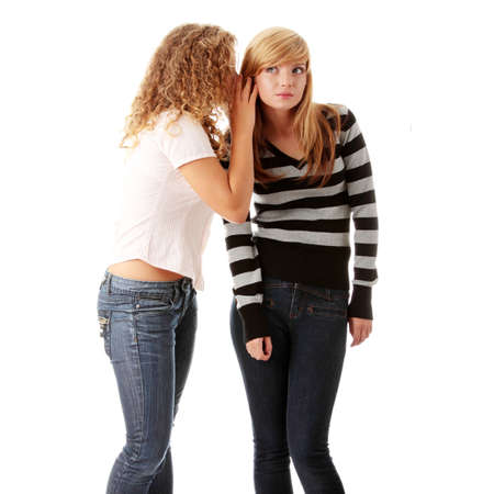 blab: Two happy young girlfriends talking isolated over white