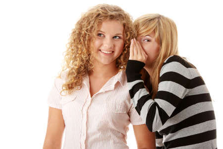 Two happy young girlfriends talking isolated over white  Stock Photo - 5978447