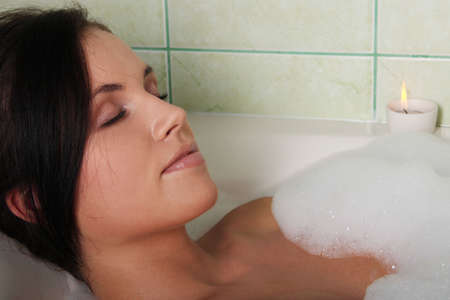 Young beautiful woman in the bathroom taking a bath  photo