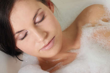 lying in bathtub: Young beautiful woman in the bathroom taking a bath