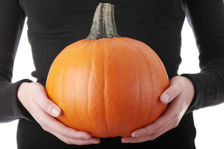 Young woman holding orange pumpkin close up,isolated photo