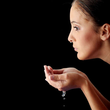Young teen woman washing her face with clean water Stock Photo - 5939374
