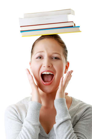 Young caucasian woman (student) with books on her head screaming with fear photo