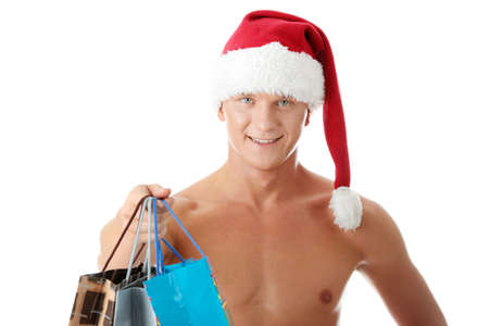 Sexy muscular shirtless man in Santa Claus hat with shopping bags isolated on white   photo