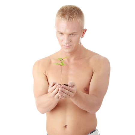 potency: Muscular man holding small plant and soil in his hands. Isolated on white in studio.