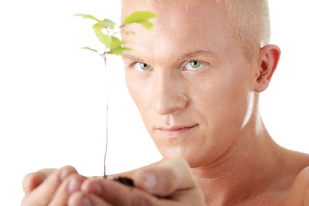 Muscular man holding small plant and soil in his hands. Isolated on white in studio. photo