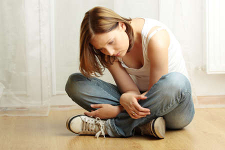 Young female sitting on the flor, stressed out, depressed and tired photo