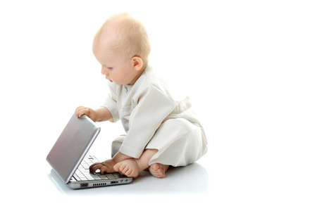 educacion gratis: Beb� con ordenador port�til sobre el fondo blanco Foto de archivo