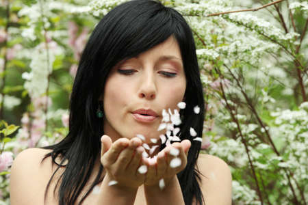 Girl blows off petals from hands  photo