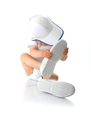 Adorable baby trying on shoes and basebal cap that are way too big for him Stock Photo