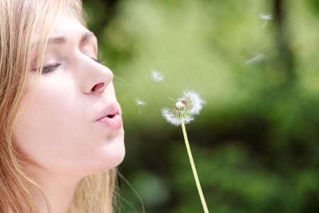 The blonde sits in park on a grass with a dandelion in hands and blowing photo